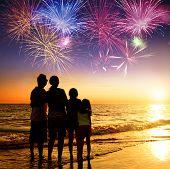 stock photo of children beach  - happy family watching the sunset and firework on the beach - JPG