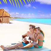image of couple sitting beach  - Blond couple sitting in the Cancun beach sand playing guitar photo mount - JPG