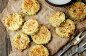 stock photo of crisps  - baked parmesan zucchini crisps on a dark wood background - JPG