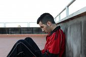foto of sob  - downcast young guy sitting at the floor against the wall - JPG