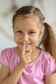stock photo of hush  - Portrait of a nice little girl showing hush sign - JPG