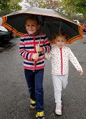 picture of brother sister  - Little brother and sister under umbrella during rain - JPG