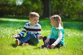 stock photo of brother sister  - Happy little brother and sister playing on grass in park - JPG