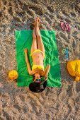 pic of top-hat  - Woman in swimsuit and hat lying on the green towel on the beach - JPG