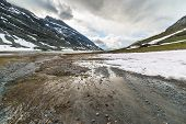stock photo of italian alps  - Flowing waters from melting snow feeding high altitude alpine lake in idyllic uncontaminated environment once covered by glaciers in the italian french Alps - JPG