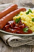 pic of mashed potatoes  - sausages mashed potatoes and beans in tomato sauce on a wooden background - JPG