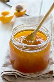 picture of apricot  - Apricot jam in a glass jar apricots and linen napkin on wooden background - JPG