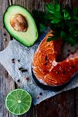 stock photo of over counter  - Salmon steak red fish avocado lime and parsley over old wooden texture  - JPG