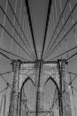 stock photo of brooklyn bridge  - A view of the arches of Brooklyn Bridge in NYC with the bridge sky and city in black and white - JPG