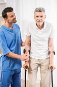 picture of male nurses  - Kind male nurse helping senior patient on ctutches - JPG