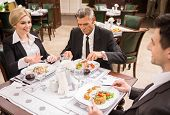 foto of lunch  - Group of successful business people discussing contract during business lunch - JPG