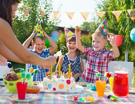 stock photo of birthday hat  - Group of adorable kids having fun at birthday party