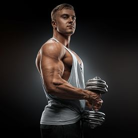 stock photo of bicep  - Strong athlete in activewear ready to doing pumping up muscles with dumbbell confidently looking forward - JPG