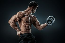 pic of shoulder muscle  - Handsome power athletic man in training pumping up muscles with dumbbell - JPG