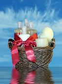 stock photo of gift basket  - photo of a gift basket full of bath accessories with isolated via clipping path on a blue sky background with reflection in water - JPG