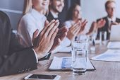 Smiling People Clap Their Hands At Conference. Mobile Phone And Glass Of Water Closeup. Blur Image I poster