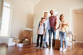 Excited Family In Lounge Of New Home On Moving Day poster