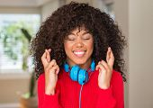 African american woman wearing headphones smiling crossing fingers with hope and eyes closed. Luck a poster