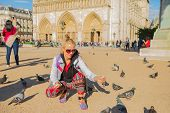Happy Young Tourist Woman Feeds Pigeons In Notre Dame Square. Caucasian Lifestyle Traveler Enjoys In poster