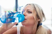 Young Blonde Woman Drinking Water After Fitness Sport poster
