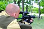A Man Hunter Is Aiming From A Gun In The Forest. Sighting The Gun Barrel At The Target. poster