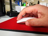 Male Hand Using A White Computer Mouse On A Red Mouse Pad poster
