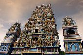 Picture of hindu temple with all colored statutes and two menaas.