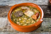pic of pot-bellied  - typical northern spain dish made with beans cabbage and pork meat served in traditional clay pot - JPG