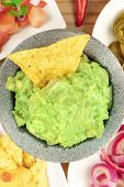 A Closeup Overhead Photo Of Guacamole Sauce In A Molcajete, Traditional Mexican Mortar, With A Nacho poster