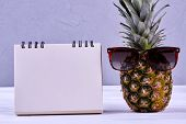 Pineapple In Sungasses And Blank Paper Notepad. Whole Green Ananas And Empty Paper Notebook. Plannin poster