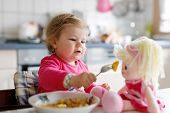 Adorable Baby Girl Eating From Fork Vegetables And Pasta. Little Child Feeding And Playing With Toy  poster