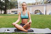 Relaxed young sportswoman dressed in sportswear meditating while sitting on a fitness mat on grass o poster