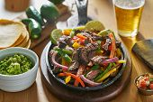 mexican beef fajitas in iron skillet with guacamole and beer poster