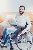Feeling Confident. Cheerful Smart Freelance Designer Sitting In Wheelchair And Feeling Glad While Wo poster
