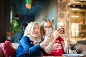 Two Young Women In A Cafe At A Table Do Selfie On Phones. Visitors To The Restaurant Take Pictures O poster