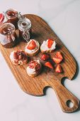 Top View Of Cutting Board With Fruit Jam In Jars And Sandwiches With Cream Cheese And Jam On Marble  poster