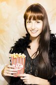 stock photo of matinee  - Happy smiling young woman in a feather boa holds an iconic traditional red and white striped box of delicious hot buttered popcorn during the intermission at showtime - JPG