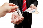 picture of bartering  - Businessman hands giving each other keys and money - JPG