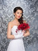 stock photo of terrific  - Young and beautiful bride standing with the flower bouquet over the grey background - JPG