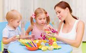 stock photo of daycare  - Two little kids with young teacher paint Easter eggs - JPG