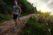 Young man with wet singlet running on a rural road during sunset