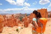 image of hoodoo  - Hiker woman in Bryce Canyon hiking looking and enjoying view during her hike wearing hikers backpack - JPG