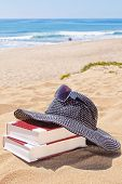 stock photo of panama hat  - Panama for the sun and reading books on the beach against the sea - JPG