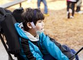 stock photo of biracial  - Biracial six year old disabled boy sitting in wheelchair while playing on playground - JPG