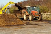 stock photo of spreader  - agricultural scene of farmer loading his commercial muck spreader with manure before fertilising his field - JPG