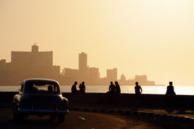 stock photo of malecon  - Skyline in La Habana Cuba at sunset with vintage cars on the street and people sitting on the Malecon - JPG