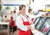 pic of apron  - Portrait of confident female butcher standing arms crossed with colleagues in background - JPG