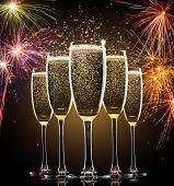 picture of champagne glasses  - Glasses of champagne with firework on background - JPG