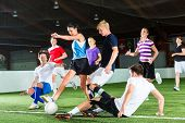 picture of indoor games  - Men and women in mixed sport team playing football or soccer indoor and trying to score goal - JPG