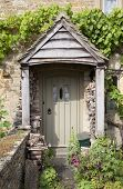 picture of english cottage garden  - Pretty English cottage doorway with logs and flowers - JPG